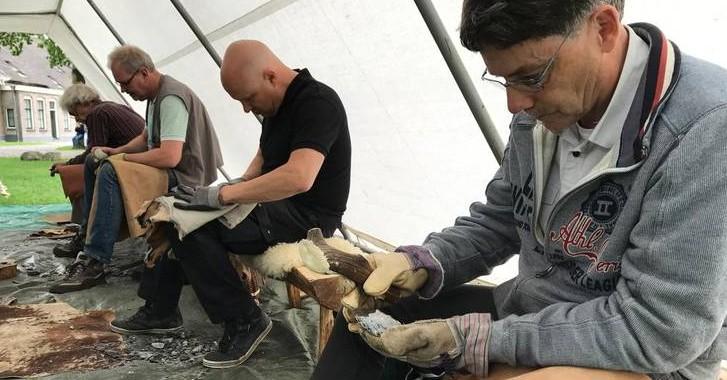 Verteller van het Oude aan het vuursteen bewerken samen met andere deelnemers tijds het NK vuistbijlen maken.