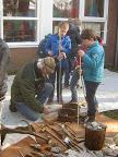 """Pijlpunten maken met leerlingen van de basisschool. Luxe hulp voor de """"Verteller van het Oude"""", Ernest Mols, Nederlands kampioen vuistbijlen maken."""